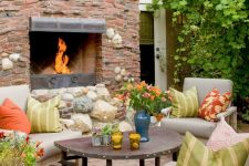 a bright Mediterranean-inspired space with a brick, stone and metal fireplace, neutral furniture with colorful pillows and bold blooms and greenery