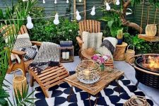 a bright and welcoming tropical patio with greenery and a tree, printed rugs and blankets, simple wooden furniture, candle lanterns and a fire pit