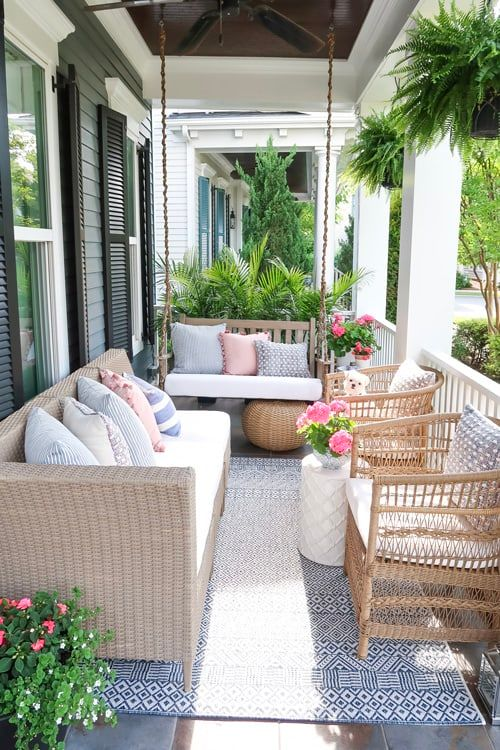 a bright farmhouse porch with light stained rattan, wood and wicker furniture, printed textiles, potted blooms and greenery is a chic and bold summer nook