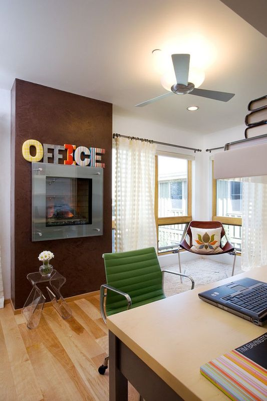 a bright home office with larrge windows, a built-in fireplace with decor, a large desk, catchy chairs and an acrylic stool