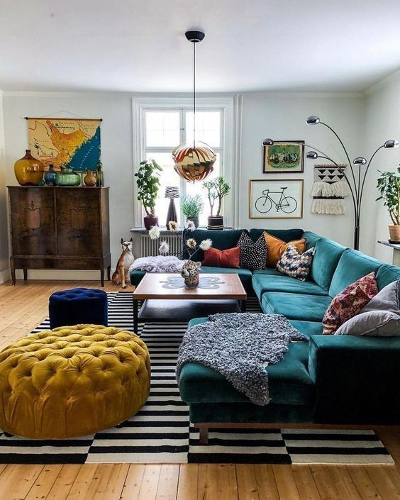 a bright mid-century modern living room with a stained storage unit, a dark green sectional, a yellow ottoman and a navy pouf, colorful pillows and a bold gallery wall