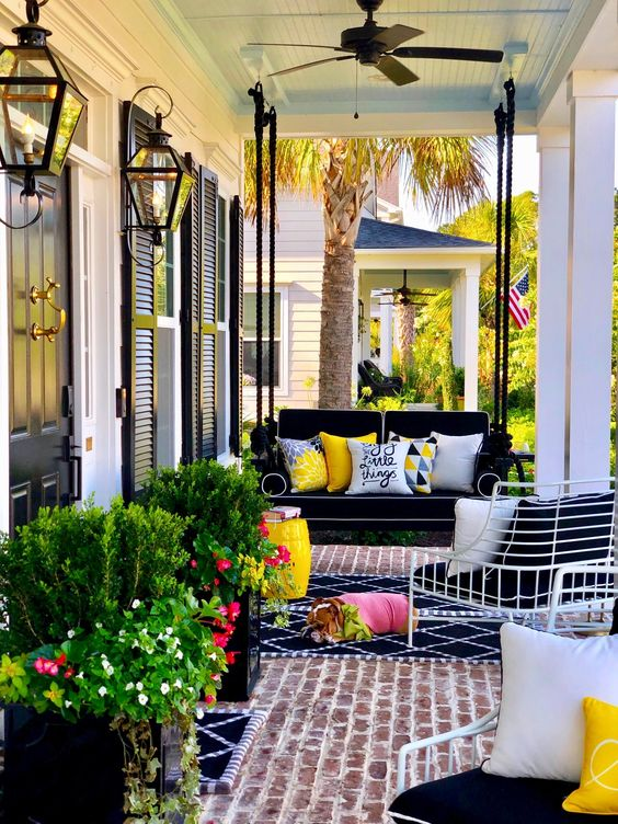 a bright porch with a black hanging daybed, a delicate bench with black and white cushions, potted greenery and blooms