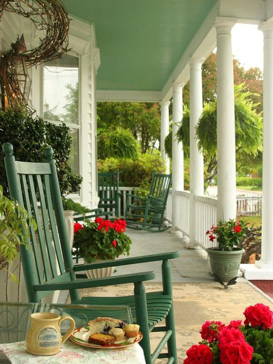 a bright rustic porch with green rockers, potted blooms and greenery and string lights is a lovely space to be