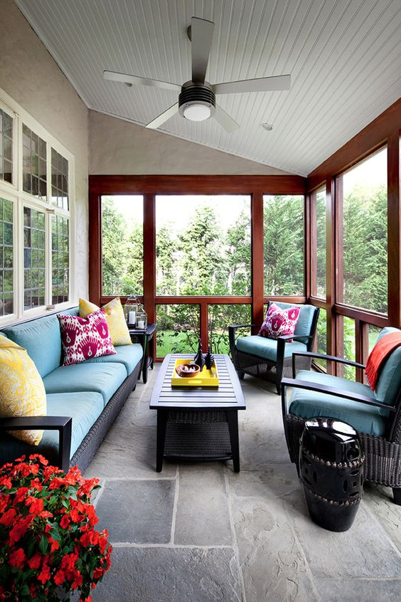 a bright traditional screened porch with black wicker furniture, bright pillows, a low coffee table, bright potted blooms