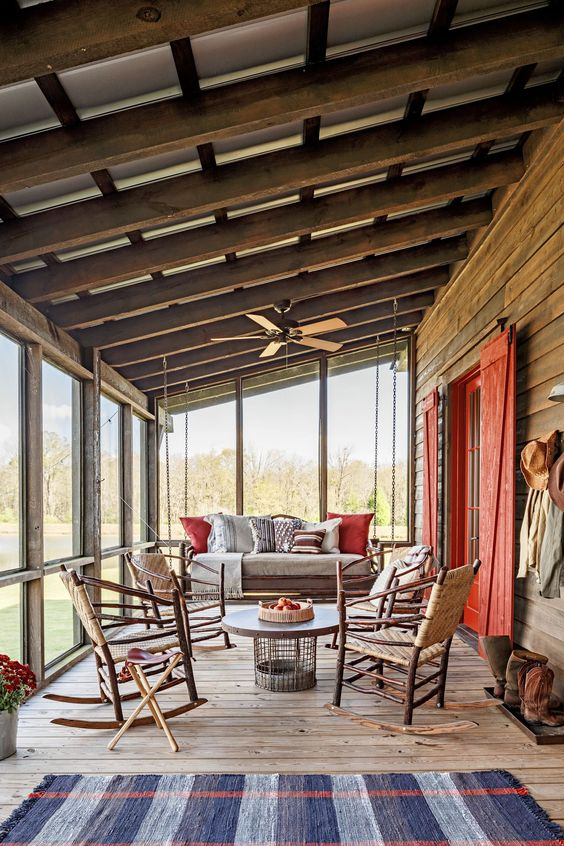 a cabin screened porch with rattan and woven furniture, a round coffee table, bright pillows, potted plants and blooms