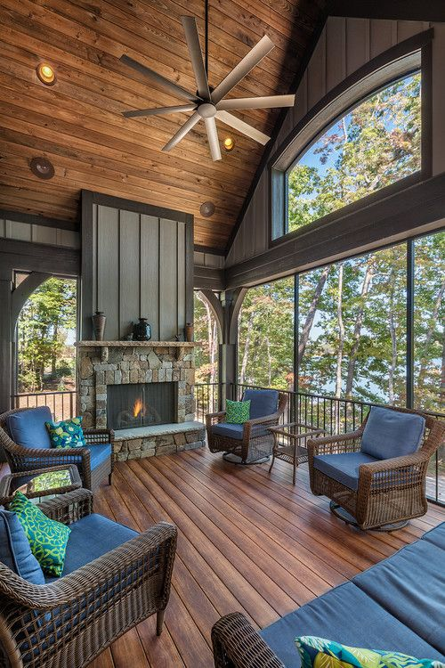 a chalet-inspired screened porch with a fireplace clad with stone, dark wicker furniture, blue and green upholstery and gorgeous views