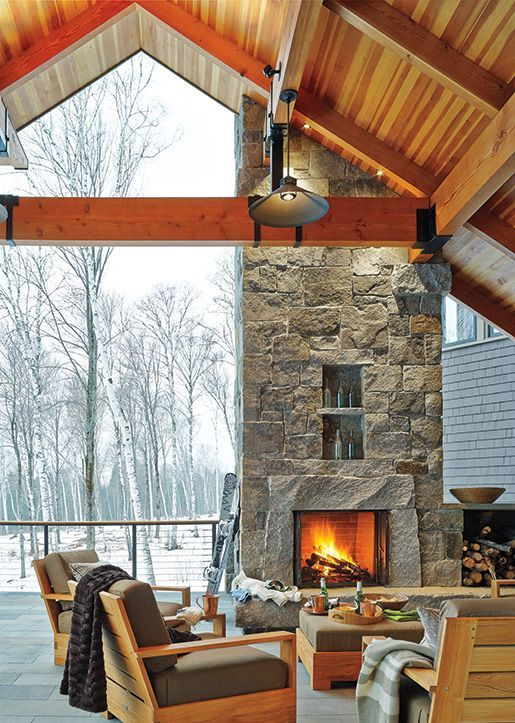 a chalet terrace with a stone fireplace, modern light stained furniture with grey upholstery and neutral and printed textiles is cool