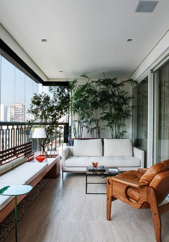 a chic and bold modern balcony as an outdoor living room, with potted plants, a white sofa and an upholstered bench, a wood and leather chair and bright accents