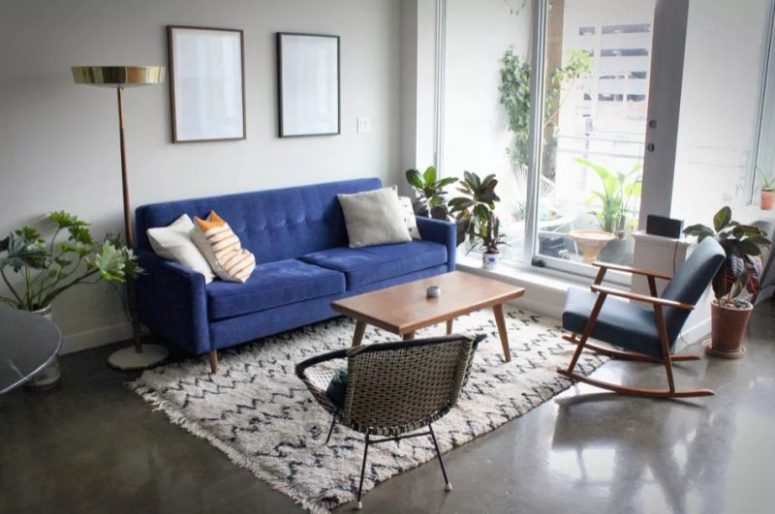 a chic and simple mid-century modern living room with a bold blue sofa, a woven chair, a printed rug and pillows and statement plants