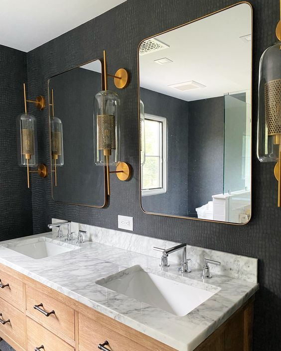 a chic bathroom with a black wallpaper wlal, brass, silver and black metals that look elegant and cohesive in the space