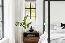 a chic bedroom in white and grey, with a black canopy bed and black French windows, neutral textiles and black lamps