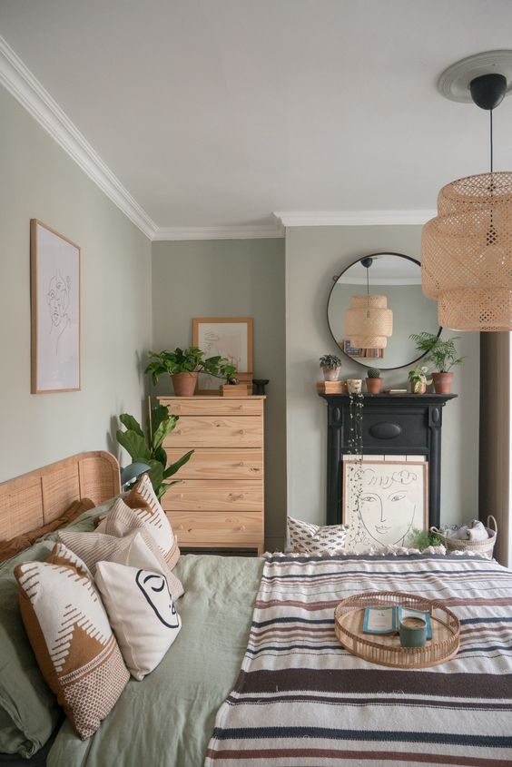 a chic bedroom with light green walls, stained furniture, printed bedding, a non wokring fireplace with an artwork, a woven pendant lamp