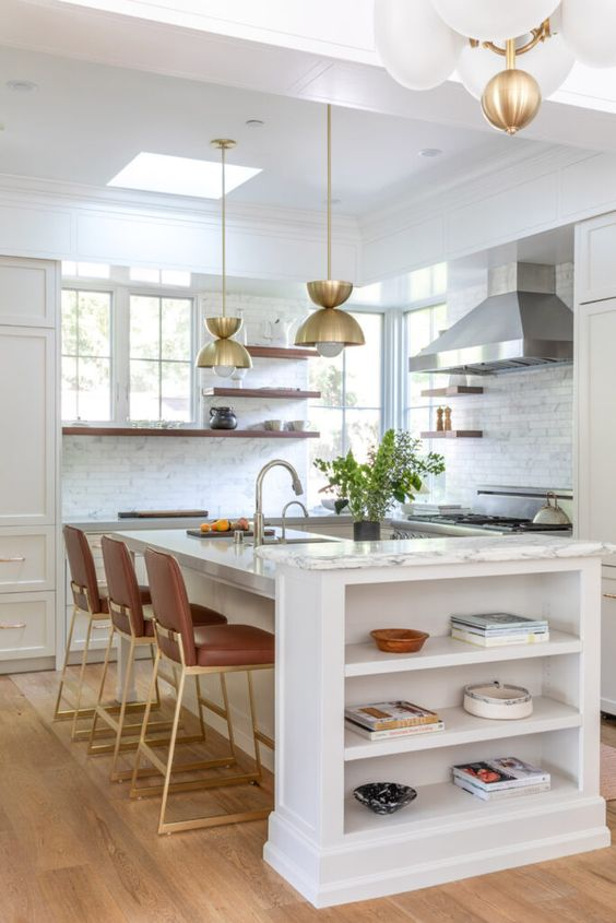 a chic farmhouse kitchen in white, with shaker cabinets, open shelves, brown stools with gold legs, gold pendant lamps and chromatic appliances