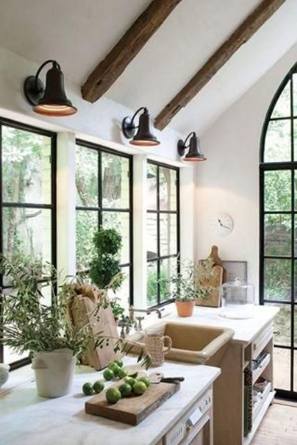 a chic farmhouse kitchen with black French windows, neutral wooden cabinets, black sconces, wooden beams on the ceiling and greenery