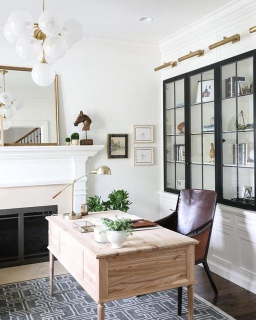 a chic home office with a built-in fireplace and a mantel, a mirror, greeneyr and art, a light stained desk, a leather chair and touches of brass