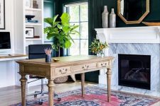 a chic home office with black paneling, niche shelves, a fireplace clad with marble, a rustic vintage desk, a boho rug and potted plants