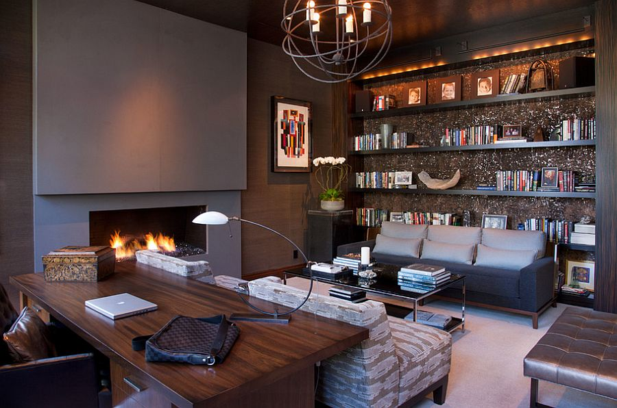 a chic home office with grey walls and a built in fireplace, built in shelves, grey seating furniture, a glass coffee table, a stained desk and leather chairs