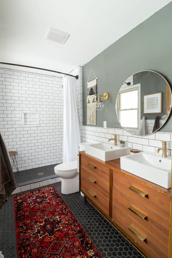 a chic mid-century modern bathroom with a grey accent wallpenny and subway tiles, a stained vanity, a round mirror and two sinks