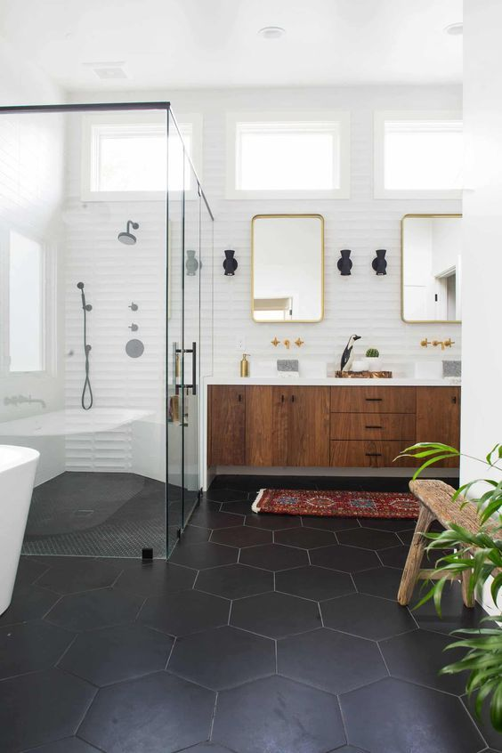 a chic mid-century modern bathroom with black hexagon tiles, a rich-stained floating vanity, a shower space, mirrors and a cool tub