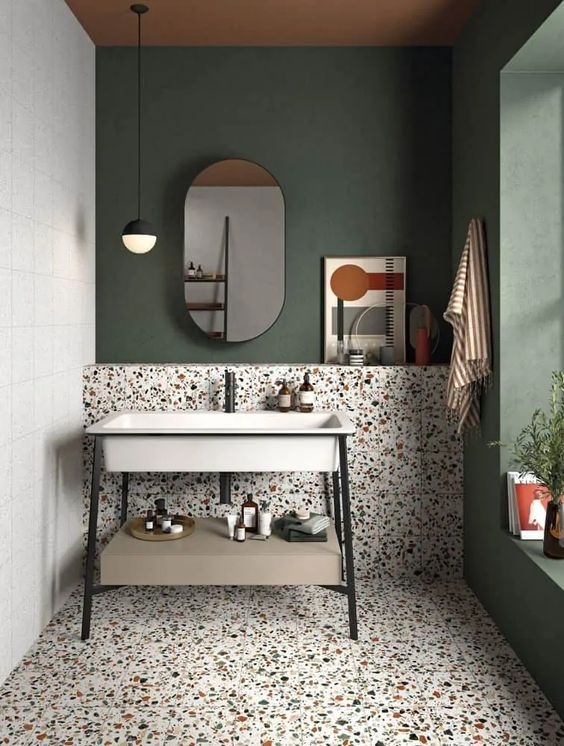a chic mid-century modern bathroom with green walls, colorful terrazzo tiles on the wall and floor, a cool modern vanity with a metal sink