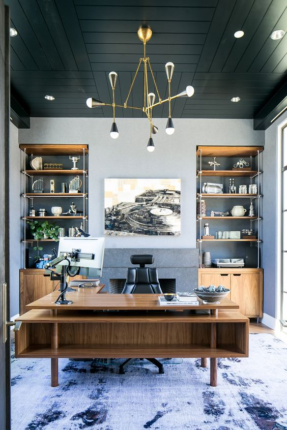a chic mid-century modern home office with light grey walls, a black planked ceiling, a catchy chandelier, light stained bookcases and a matching desk, a dip dyed rug and a black chair