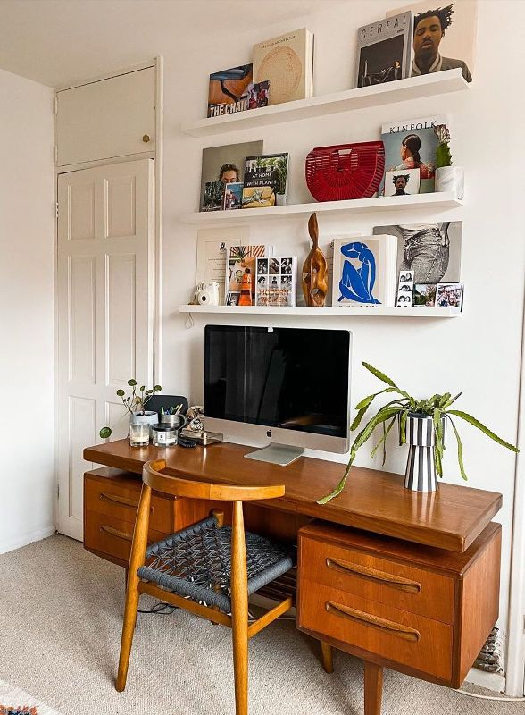 a chic mid-century modern home office with open shelves, a stained desk, a woven chair, bold decor and accessories is cool