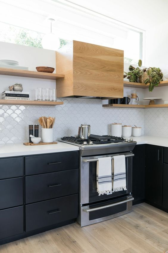 a chic mid-century modern kitchen with black cabinets, white countertops, white Moroccan tiles, light stained shelves
