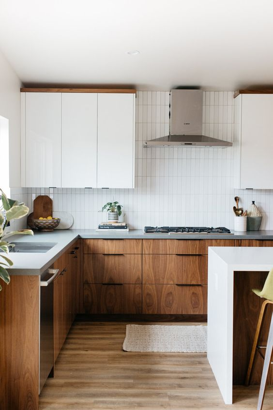 a chic mid-century modern kitchen with two tone cabinets, grey stone countertops, a white skinny tile backsplash and neutral fixtures
