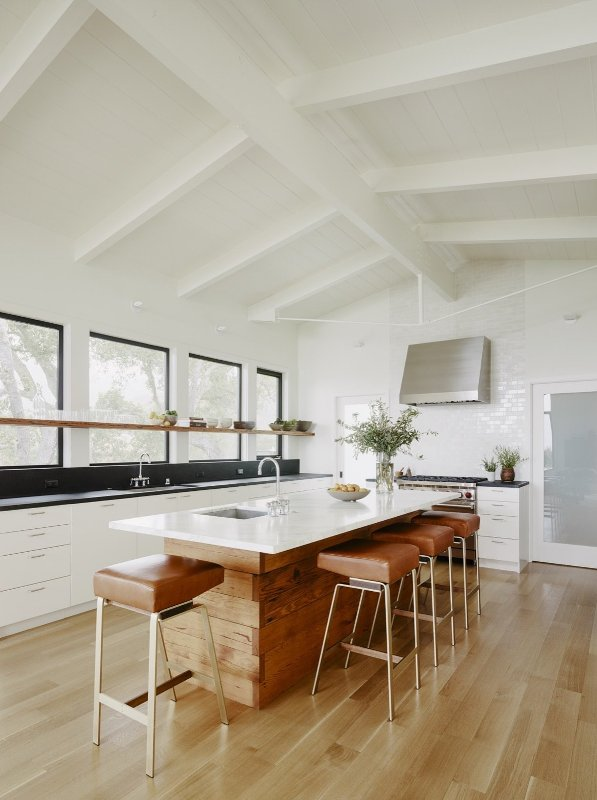 a chic mid-century modern kitchen with white cabinets, black countertops and a backsplash, a wooden kitchen island and leather stools