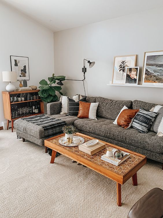 a chic mid-century modern living room with a grey sectional, stained furniture, potted plants, a gallery wall on a ledge is very cozy