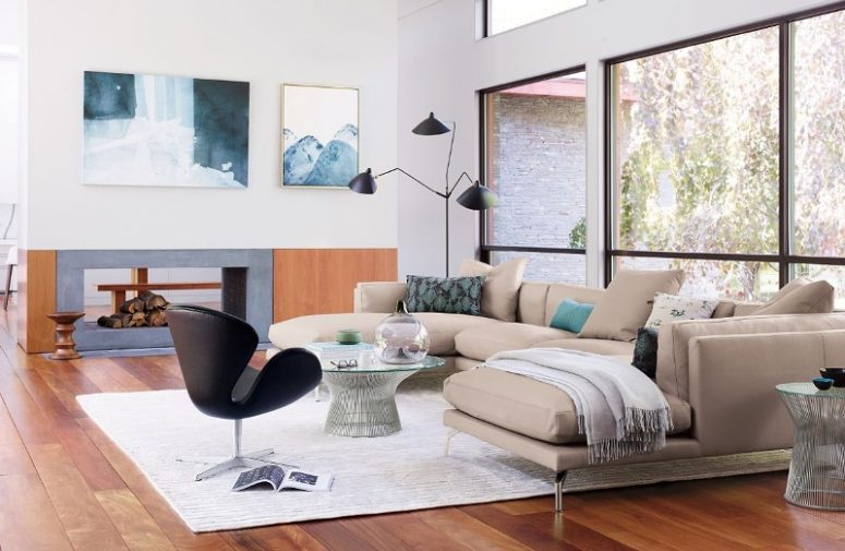 a chic mid-century modern living room with a tan sectional, a black chair, a glass table, a black floor lamp, a double-sided fireplace and cool art