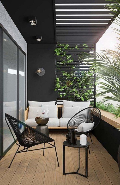 a chic modern balcony done in black and white, with a neutral stained sofa, black chairs, a black round table and lots of greneery