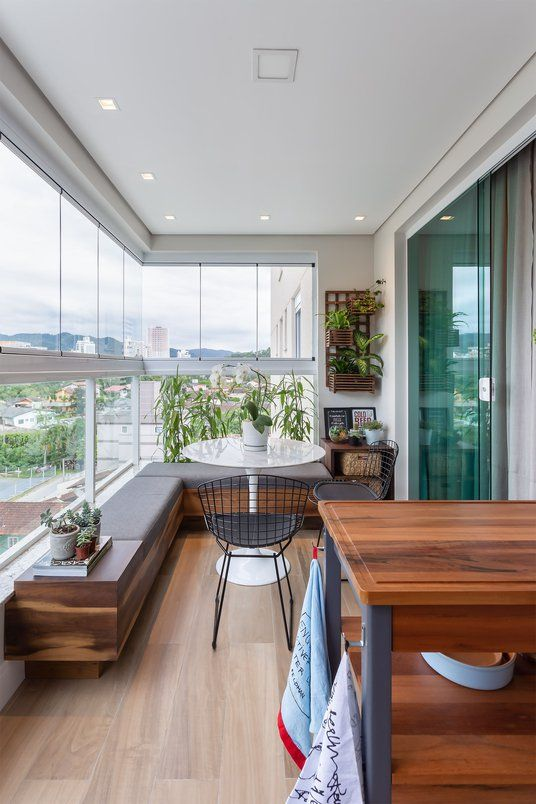 a chic modern balcony with a built-in upholstered bench, metal chairs, a round table, potted greenery, a cart for cooking or serving drinks