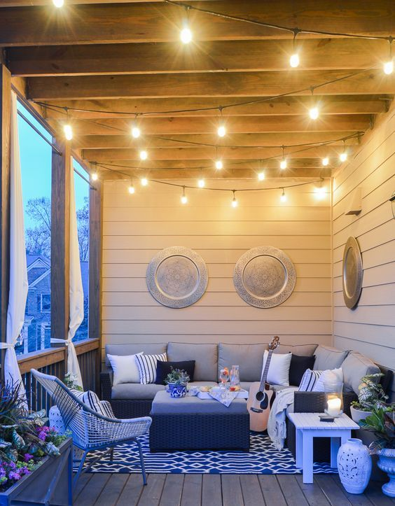 a chic modern boho porch with a wicker sectional sofa, a low coffee table, a woven chair, some stools, potted plants and lights