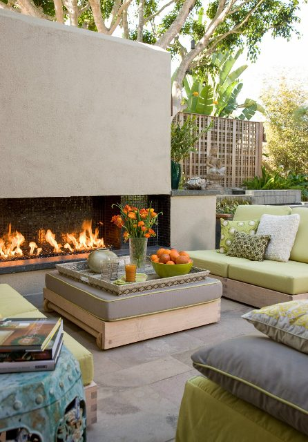a chic modern outdoor space wiht a fireplace, neutral furniture wiht green and grey upholstery, a large ottoman and bold touches of orange