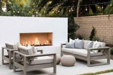 a chic modern space by the pool – a modern sleek fireplace in white, neutral stained and neutral upholstery furniture, jute poufs is a gorgeous nook