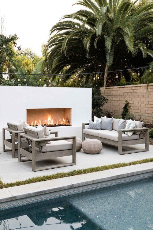 a chic modern space by the pool   a modern sleek fireplace in white, neutral stained and neutral upholstery furniture, jute poufs is a gorgeous nook