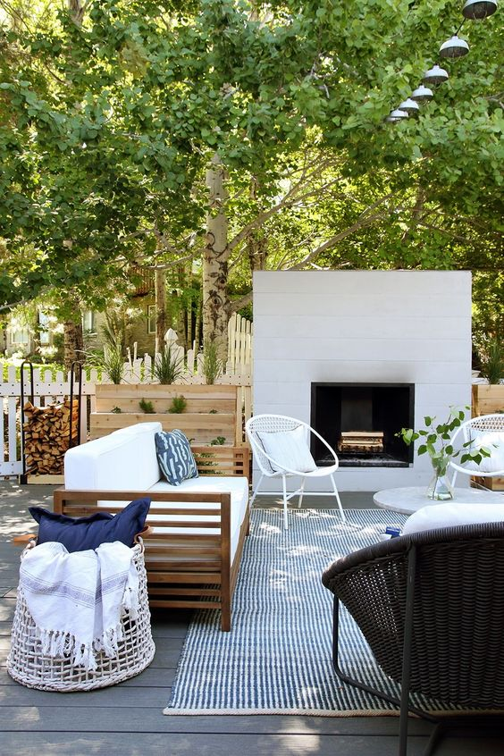 a chic modern terrace with a white fireplace, rattan and wood furniture, neutral upholstery and printed textiles is amazing