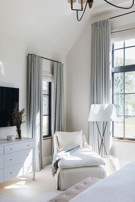 a chic neutral bedroom done in white and light grey, with black French windows, touches of black for more drama is wow
