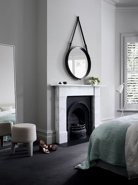 a chic neutral bedroom with a built-in fireplace, a hanging round mirror, a bed with pastel and neutral bedding, a creamy stool and a mirror