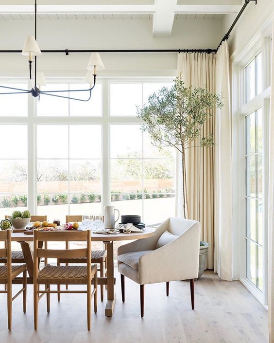 a chic neutral dining room with French windows, a trestle wooden table, woven chairs, a chic chandelier and neutral curtains is amazing