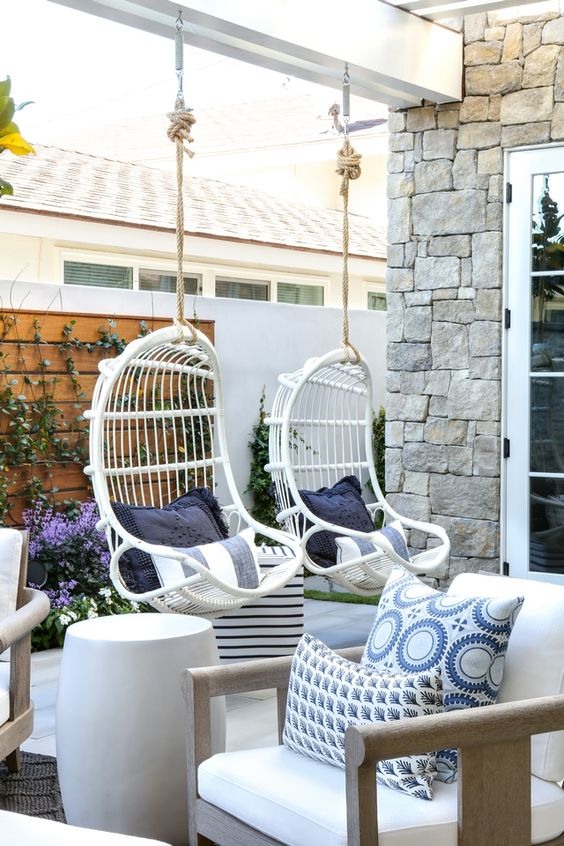 a chic terrace with a white rattan hanging chairs with printed pillows, neutral furniture, potted plants and blooms
