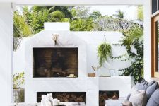 a chic terrace with a wooden deck, a fireplace and firewood storage, a wooden coffee table, poufs and printed textiles