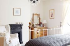 a chic vintage bedroom with a metal built-in fireplac,e a white metal bed, a stained dresser, a vintage chair and a beautiful crystal chandelier