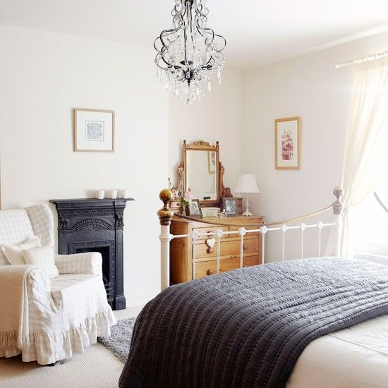 a chic vintage bedroom with a metal built in fireplac,e a white metal bed, a stained dresser, a vintage chair and a beautiful crystal chandelier
