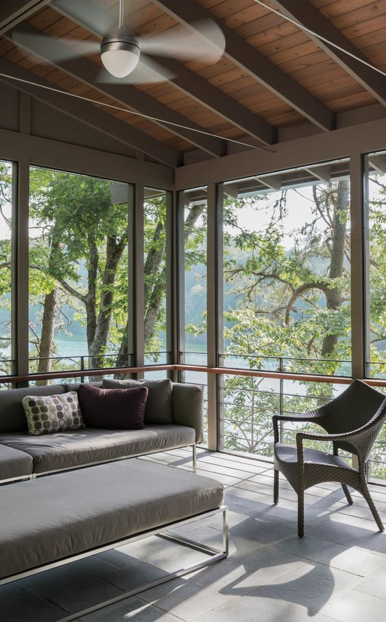 a clean and lovely contemporary screened porch with laconic grey furniture, a wicker chair and lovely views of the lake