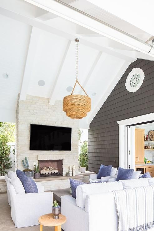 a coastal outdoor living room with a white brick fireplace, white furniture, blue pillows, a woven pendant lamp and potted plants
