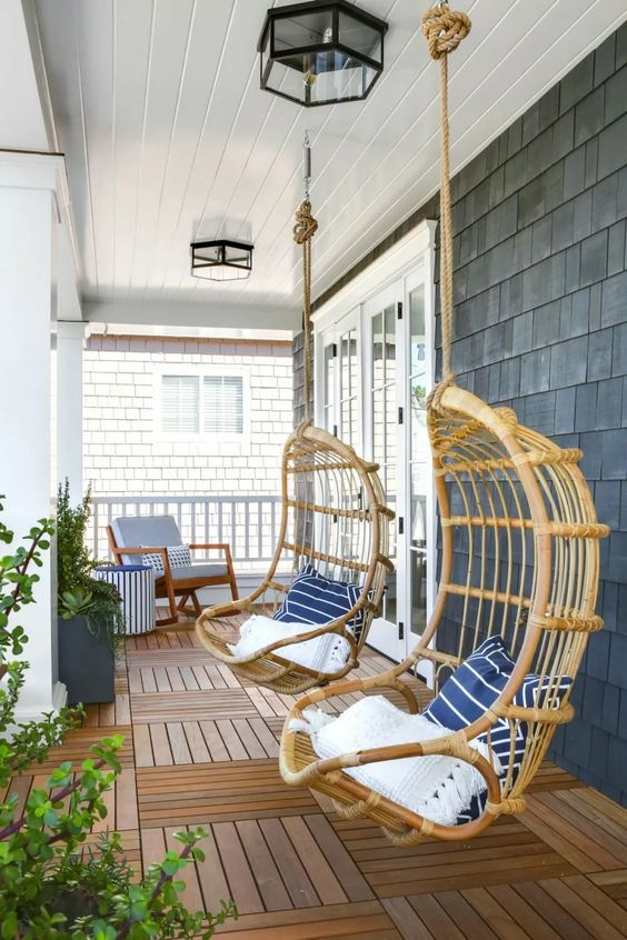 a coastal porch with a wooden deck, rattan hanging chairs with printed pillows, a rocker with a side table and lots of greenery