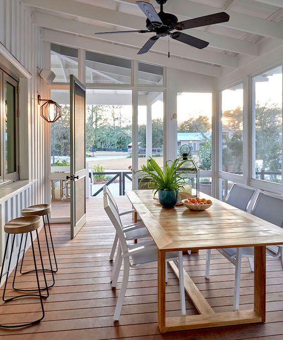 a coastal screened porch with a pass by window, a wooden dining table and white chairs plus views of the surroundings