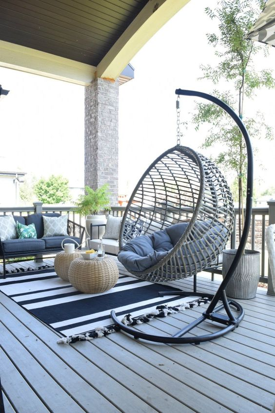 a coastal terrace with a wooden deck, rattan furniture, printed and neutral textiles, a hanging chair on a stand and wicker side tables